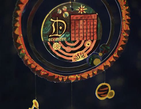 Photo sur fond noir d'un calendrier prenant la forme d'un mobile en papier. Inspiré d'illustration medievale, il a des motifs d'etoiles et de planètes, aevec des textures peintes à la gouache. Fait en 2016 par celia housset